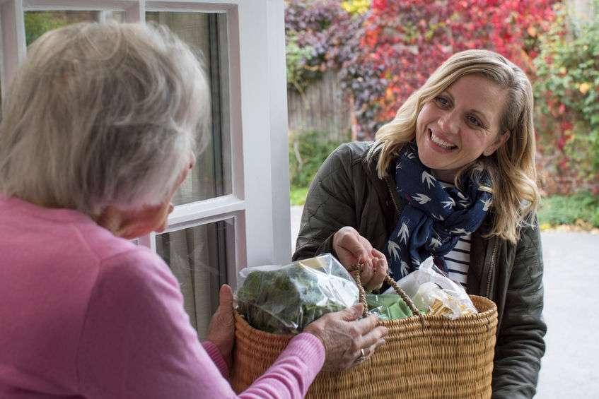 caregiver delivering groceries to senior woman