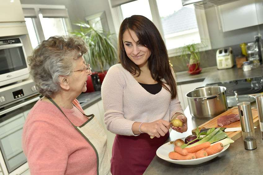 Caregiver helping senior woman prepare meal