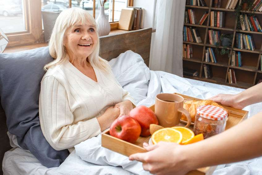 Caregiver delivering senior woman meal in recovery bed