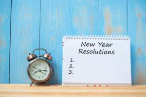 Clock and notebook with New Year Resolution list