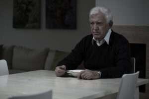 Senior Man eating alone at table