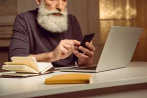 grey haired man sitting at table and using smartphone at home