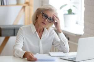 Pensive senior woman thinking of problem solution in office
